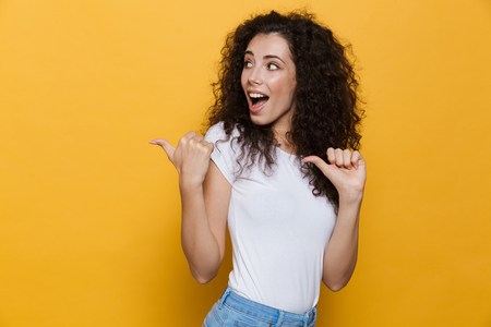 Photo of beautiful excited young cute woman posing isolated over yellow background pointing.