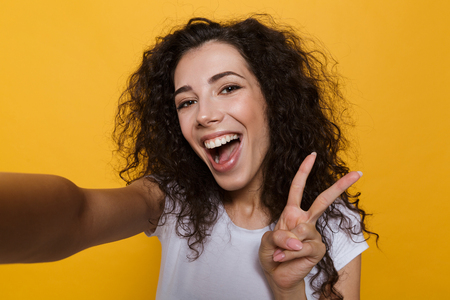 Image of an excited happy cute young woman posing isolated over yellow background take a selfie by camera showing peace gesture. Banco de Imagens