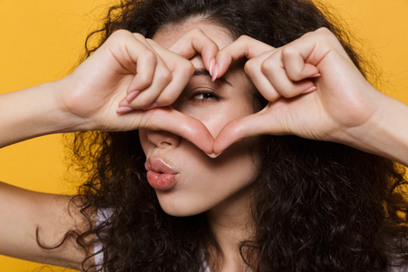 Photo of emotional young cute woman posing isolated over yellow background showing heart love gesture.