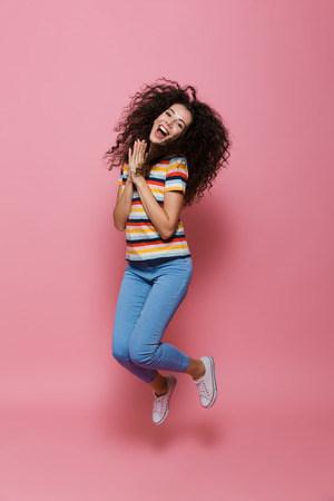 Full length photo of gorgeous woman 20s with curly hair having fun and jumping isolated over pink background