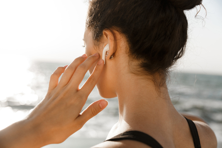 Close up back view of of young sportswoman at the seaside, listening to music with earphones