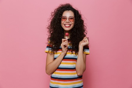 Image of an excited happy cute young woman posing isolated over pink background eat candy lollipop. Banco de Imagens