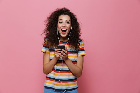 Image of an excited happy cute young woman posing isolated over pink background using mobile phone listening music.