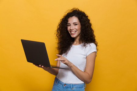 Photo of charming woman 20s wearing casual clothes smiling while holding black laptop isolated over yellow background Stock Photo