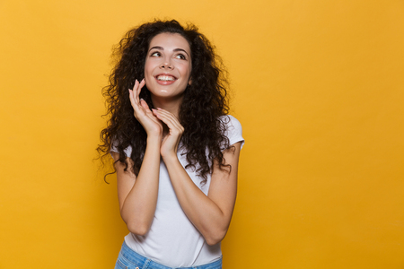 Photo of beautiful excited young cute woman posing isolated over yellow background.