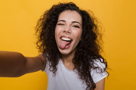 Image of an excited happy cute young woman posing isolated over yellow background take a selfie by camera showing tongue. Standard-Bild