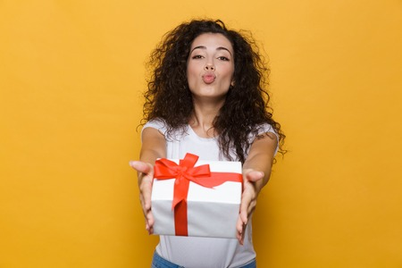 Image of a excited happy cute young woman posing isolated over yellow background holding gift box present blowing kisses.