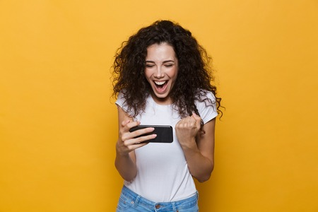 Image of an excited happy cute young woman posing isolated over yellow background play games by mobile phone make winner gesture.
