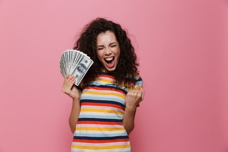 Image of pleased woman 20s with curly hair holding fan of dollar money isolated over pink background 스톡 콘텐츠