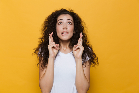 Photo of beautiful excited young cute woman posing isolated over yellow background showing hopeful please gesture.