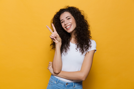 Photo of beautiful excited young cute woman posing isolated over yellow background showing peace gesture. Banco de Imagens