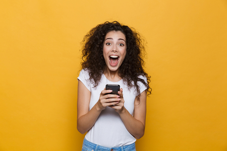 Image of an excited happy cute young woman posing isolated over yellow background using mobile phone.