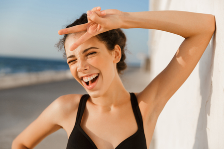 Close up of cheerful young sportswoman standing outdoors at the seaside, leaning on a wall Zdjęcie Seryjne