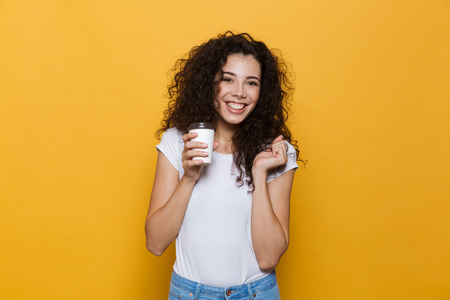Image of an excited happy cute young woman posing isolated over yellow background holding cup of coffee. Reklamní fotografie