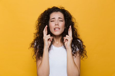 Photo of beautiful excited young cute woman posing isolated over yellow background showing hopeful please gesture. Banco de Imagens - 110904950