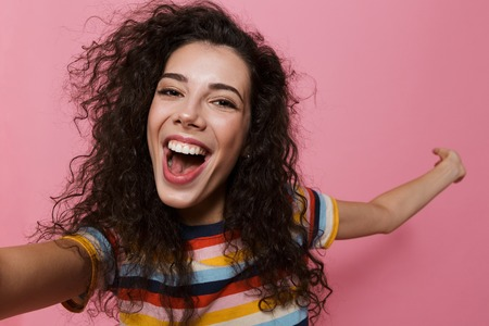 Image of an excited happy cute young woman posing isolated over pink background take a selfie by camera showing copyspace.