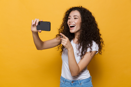 Image of an excited happy cute young woman posing isolated over yellow background take a selfie by mobile phone pointing.