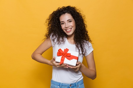 Image of a excited happy cute young woman posing isolated over yellow background holding gift box present.