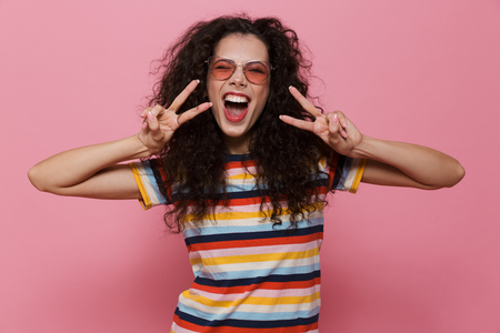 Image of happy cute young woman posing isolated over pink background make peace gesture. 版權商用圖片