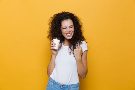 Image of an excited happy cute young woman posing isolated over yellow background holding cup of coffee. 스톡 콘텐츠