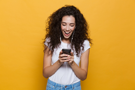 Image of an excited happy cute young woman posing isolated over yellow background using mobile phone listening music. 版權商用圖片