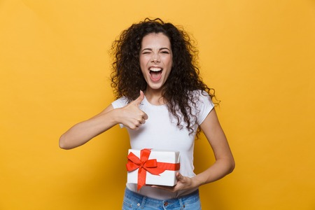 Image of excited happy cute young woman posing isolated over yellow background holding gift box present make thumbs up gesture.