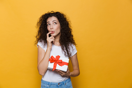 Image of a cute young woman posing isolated over yellow background holding gift box present.