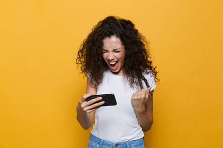 Image of an excited happy cute young woman posing isolated over yellow background play games by mobile phone.