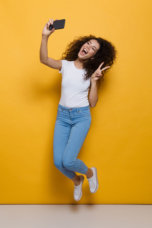 Full length photo of pretty woman 20s with curly hair holding smartphone and taking selfie photo isolated over yellow background