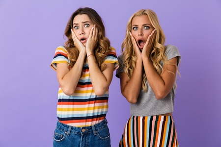Two pretty scared young girls friends standing isolated over violet background, screaming Stock Photo