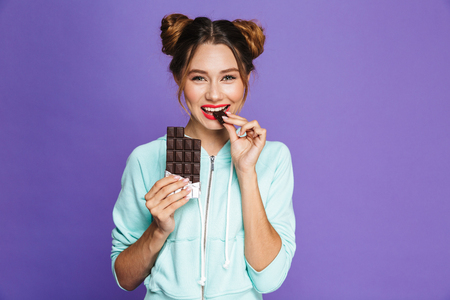 Portrait of a smiling young girl with bright makeup over violet background, eating chocolate bar