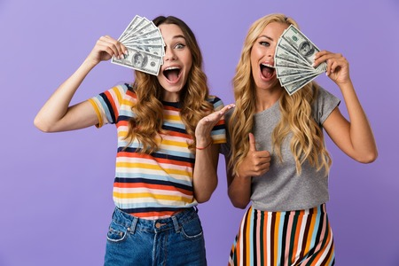 Two pretty excited young girls friends standing isolated over violet background, showing money banknotes Stock Photo