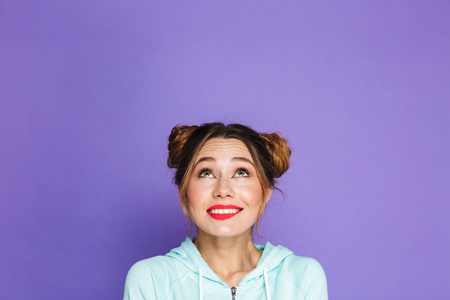 Portrait of cute cheerful girl with two buns looking upward on copyspace and twisting mouth isolated over violet background in studio