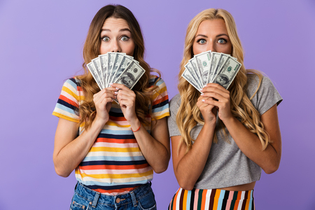 Two pretty young girls friends standing isolated over violet background, showing money banknotes Stock Photo