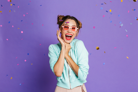 Portrait of a cheery young girl with bright makeup over violet background, celebrating under confetti shower