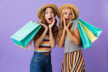 Two pretty excited young girls friends in summer hats standing isolated over violet background, carrying shopping bags