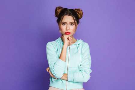 Portrait of upset woman with two buns pouting and looking offended isolated over violet background in studio