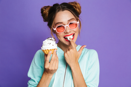 Portrait of a happy young girl with bright makeup isolated over violet background, eating cupcake Zdjęcie Seryjne