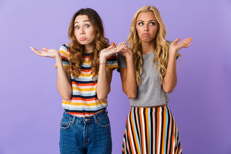Two pretty confused young girls friends standing isolated over violet background, shrugging shoulders Stock Photo