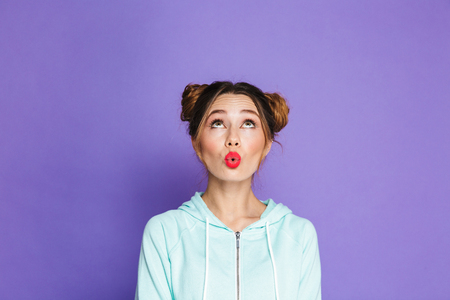 Portrait of glamour woman with two buns looking upward on copyspace and putting lips together for kissing isolated over violet background in studio