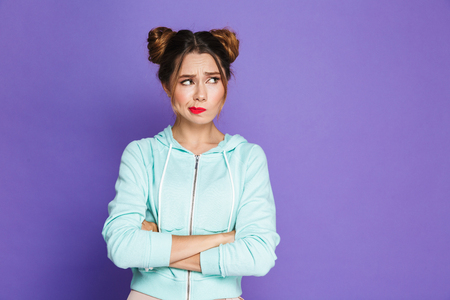 Portrait of confused woman with two buns twisting mouth and looking aside with arms crossed isolated over violet background in studio