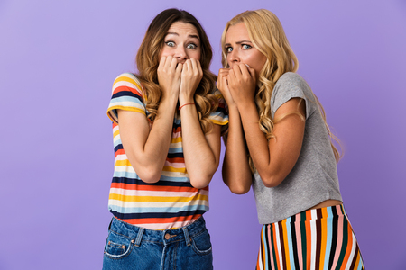 Two pretty frightened young girls friends standing isolated over violet background, cover mouth