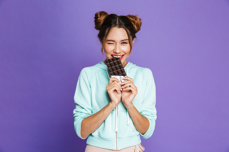 Portrait of a funny young girl with bright makeup over violet background, eating chocolate bar