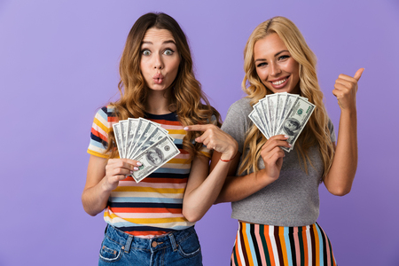 Two pretty happy young girls friends standing isolated over violet background, showing money banknotes