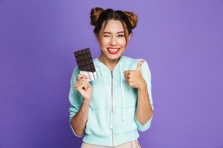 Portrait of a cheerful young girl with bright makeup over violet background, holding chocolate bar, showing thumbs up