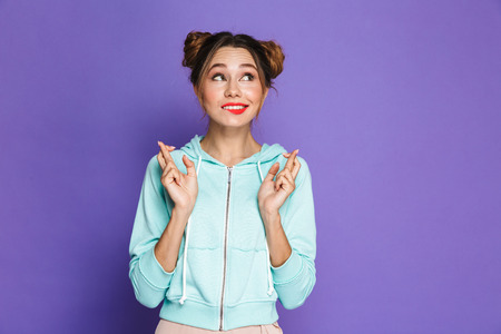 Portrait of funny young girl with two buns keeping fingers crossed and dreaming for good luck isolated over violet background in studio Stok Fotoğraf