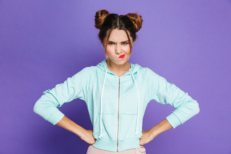 Portrait of angry woman with two buns twisting mouth with furious look isolated over violet background in studio