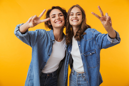Image of happy emotional young women friends posing isolated over yellow background showing peace gesture. Stock fotó