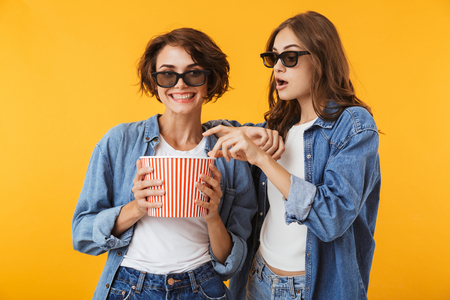 Image of happy women friends isolated over yellow wall background holding pop corn watch film.