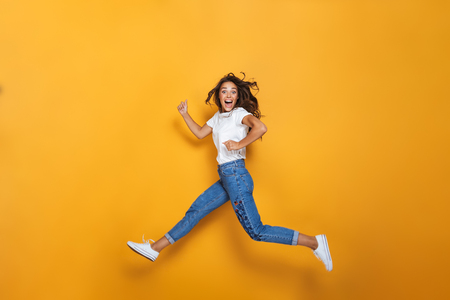 Full length portrait of a happy girl with long dark hair jumping over yellow background, looking at camera Banco de Imagens - 110904888